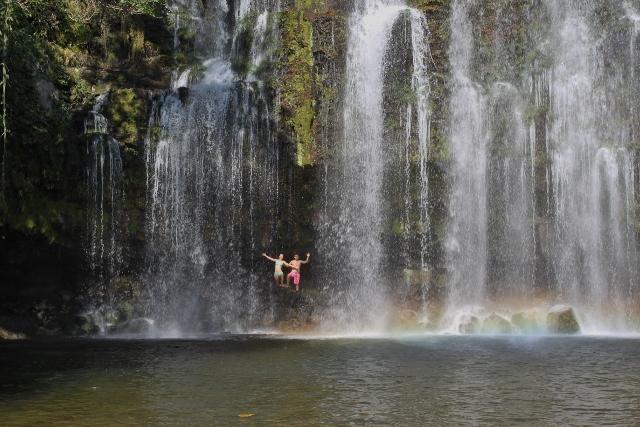 people posing behind waterfall