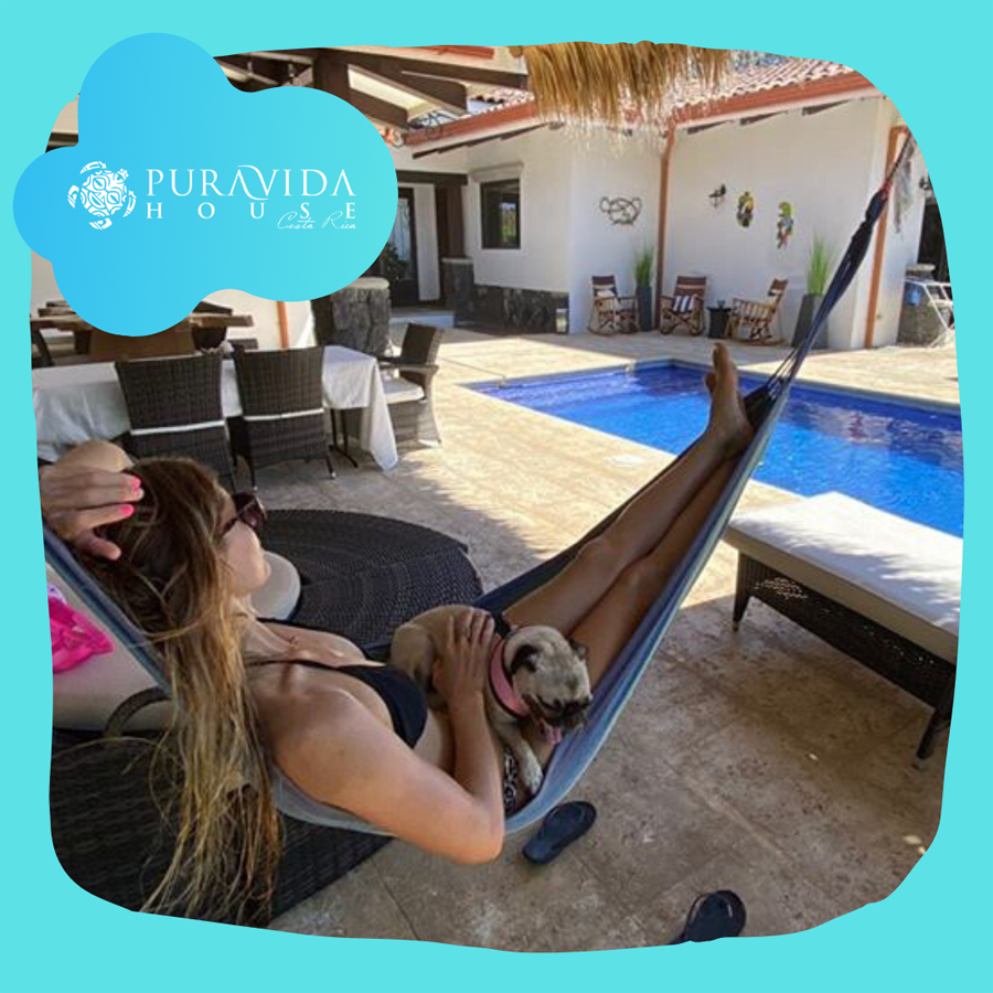 person relaxing in a hammock by the pool